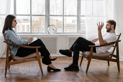 A man talking to a therapist during cognitive behavioral therapy